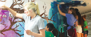 Student volunteers work tirelessly to complete the mural.
