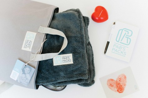PAB'S PACKS gives kids with prolonged hospital experiences comfort in the form of a cozy blanket, chapstick, lotion, a stress ball, a notebook, a handwritten note from Phillips and Nelson, and a Pabby the Penguin stuffed animal.