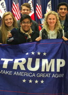 Students stand behind a Trump banner at a rally in Iowa.