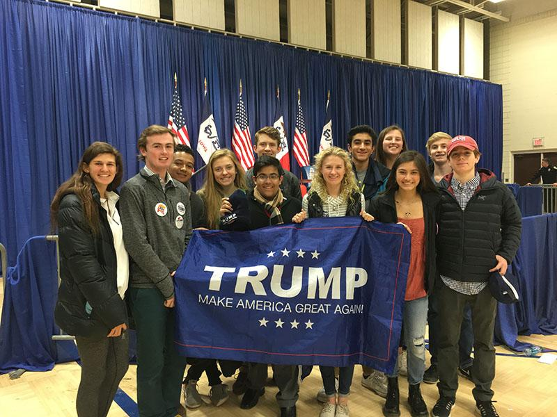 Students at the Iowa caucus pose with a Trump flag at the January 31st rally.
