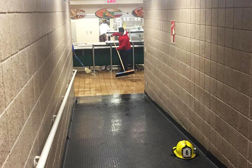 One of the Taher staff members swept standing water in the lunchroom after the pipe broke.