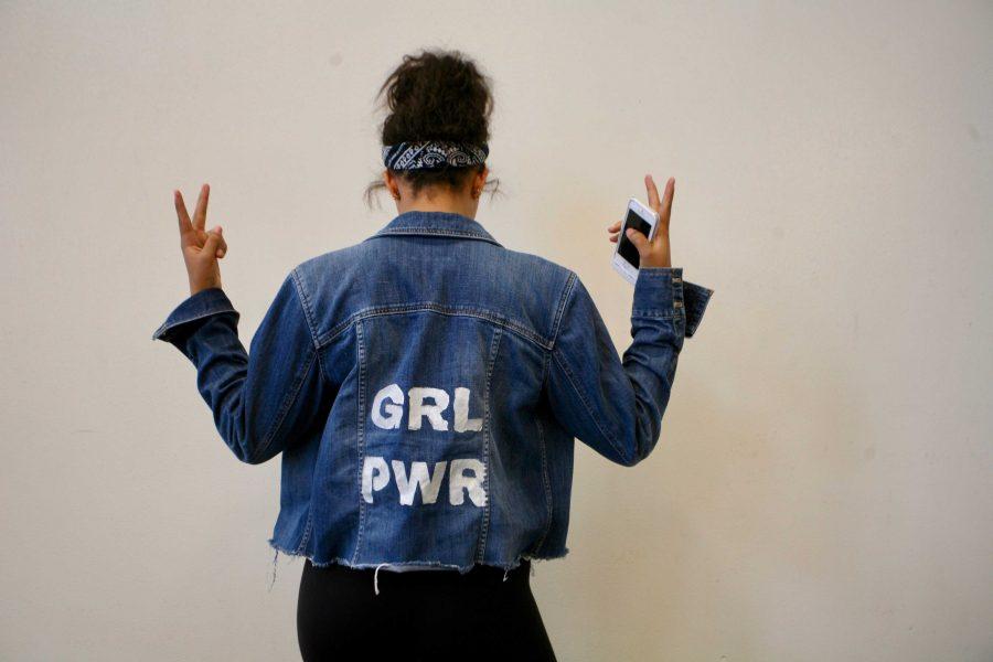 Kaja Bingham '19 shows off her handmade denim jacket in standing behind women's rights.