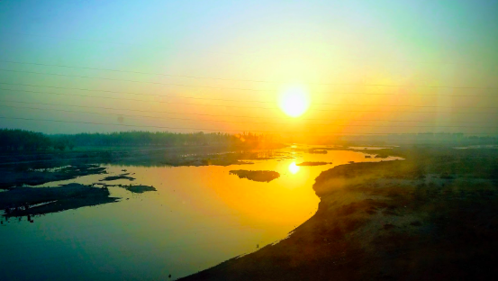 This picture was taken of a sunrise from the window of an early morning train, when heading from Amritsar to Delhi.