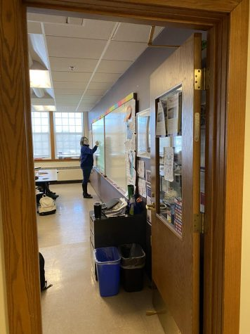 Beth Calderone stands at the whiteboard, teaching a Microeconomics class to juniors and seniors.