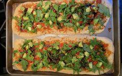 Arugula Caprese flatbread topped with avocado and balsamic glaze.
