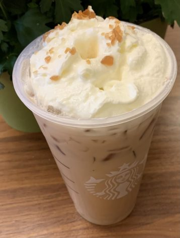 The iced caramel brûlée latte topped with whipped cream in its cup