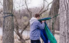 "Frederick Loew '22 hangs an ENO Hammock at Hidden Beach Park near Lake of the Isles. Even in colder weather, mocking can be fun if you bring blankets and warm clothes. It's also possible to hang hammocks above  one another to create a ""stack"" of sorts. Although slightly dangerous, it is helpful if you are in a location that isn't densley forested."